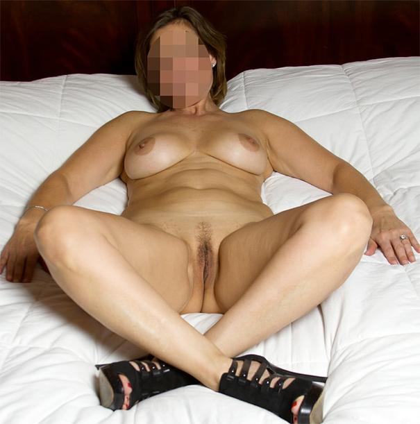 Femme mature coquine nue allongée sur un lit