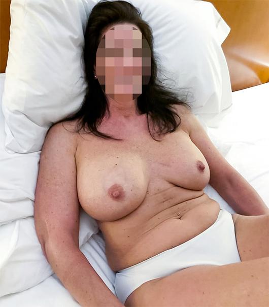 Brune à gros seins dans un lit