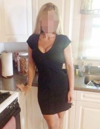 Femme mature chic en robe noire moulante
