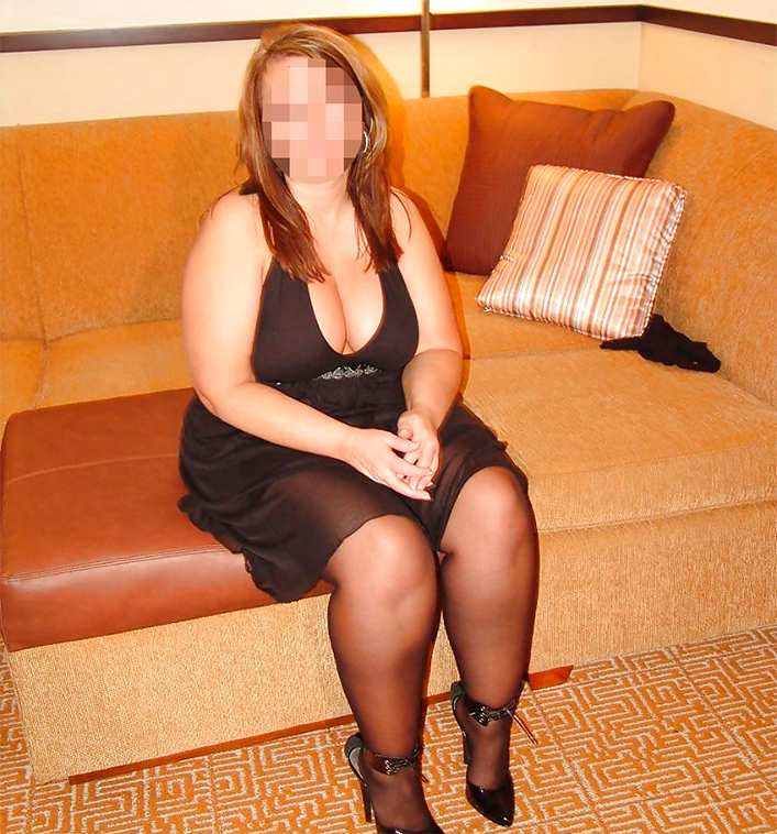 Femme cougar en robe noire et talons haut